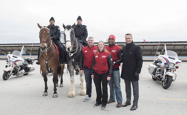 A group of people beside two horses with officers in TPS uniform