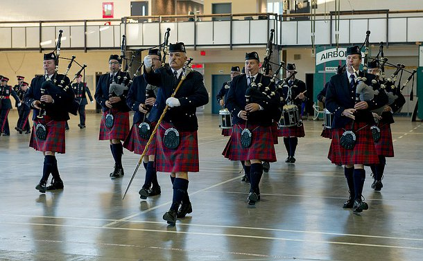 Men in kilts and bag pipes and drums marching
