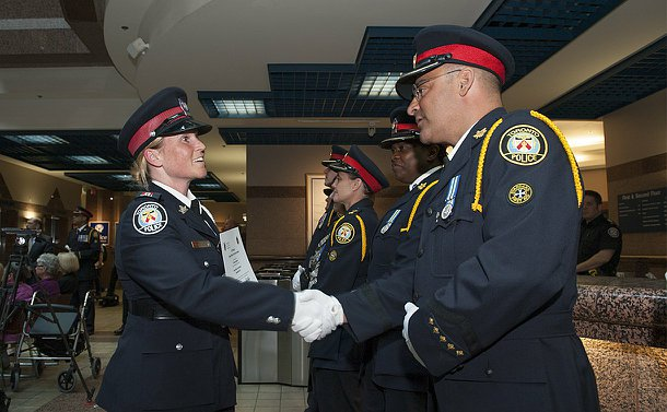 A woman in TPS uniform shakes hands with a man in TPS uniform in front of a row of officers