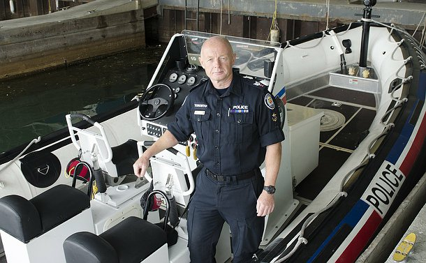A man in TPS uniform stands in a police boat