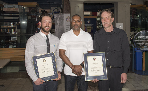 Two men holding framed certificates alongside another man