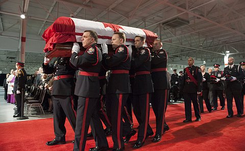 Eight men holding a flag draped casket in front of a another group