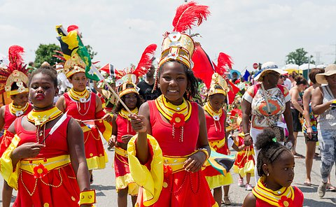 Girls in red and yellow costumes walk in a parade.