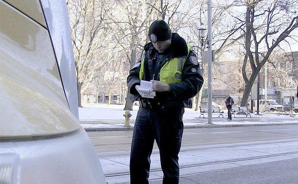 A man in TPS uniform writes a ticket beside a truck