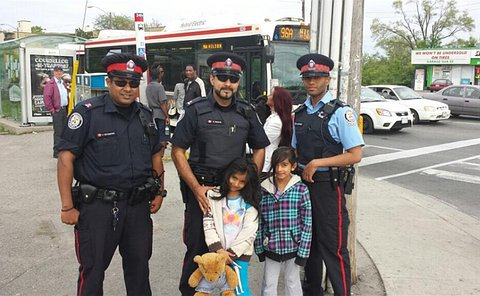 Two men in TPS uniform with two children at a bus stop