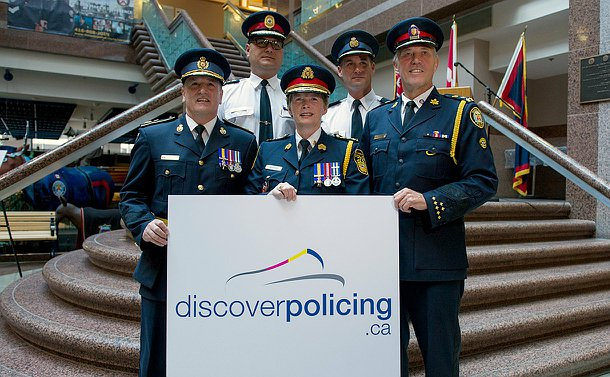 A group of four men and one women in police uniform on stairs in two rows. The first row holds a sign that states: discover policing.ca and a logo