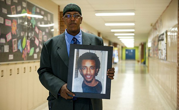 A man standing in a hallway holding a photo of another man