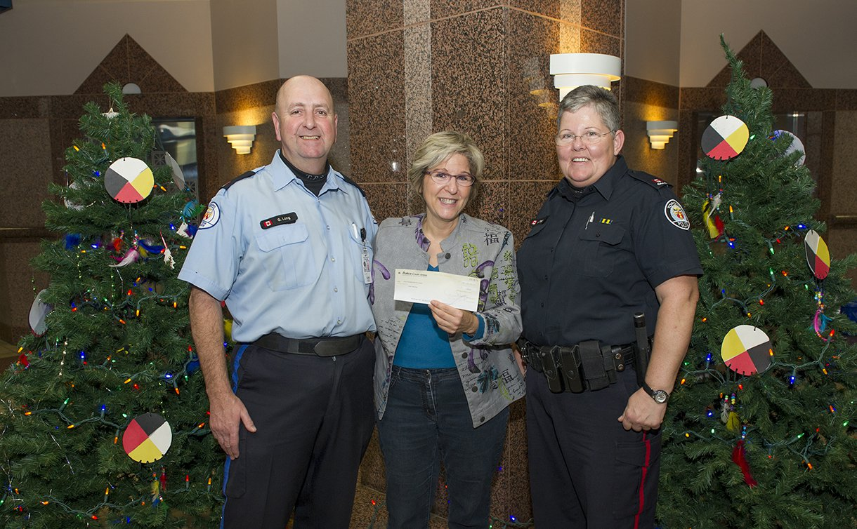 One man and two women stand in a row. Woman in centre is holding a cheque. They are flanked by Christmas trees.