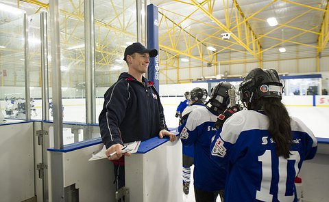 A man in a TPS baseball cap holds open the door to the rink for kids in hockey uniform