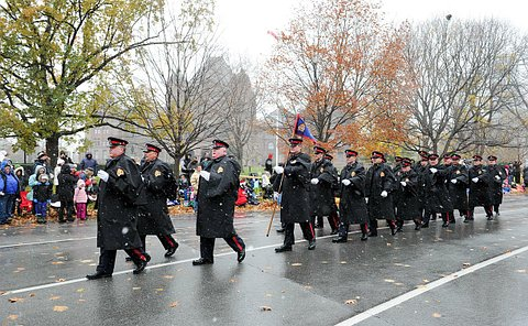 A group of men marching in a column in TPS dress uniform