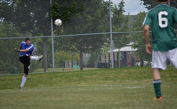 A man in soccer uniform kicks a ball as an opponent looks on