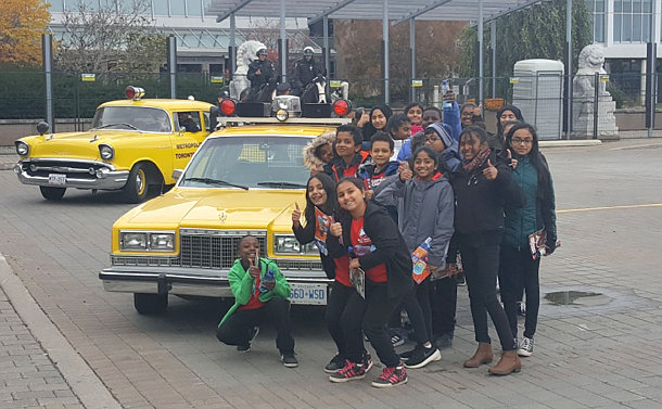 A group of kids beside a yellow TPS car