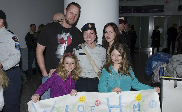 A woman in TPS uniform with two children holding a welcome home sign and a man and woman
