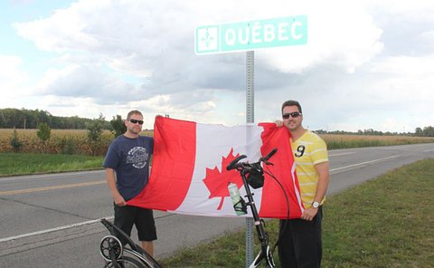Two men hold a Canada flag in front of a Quebec sign