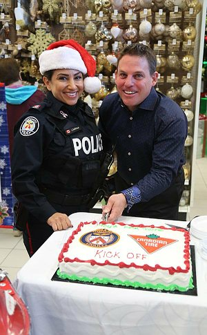A woman in TPS uniform with another man cutting a cake