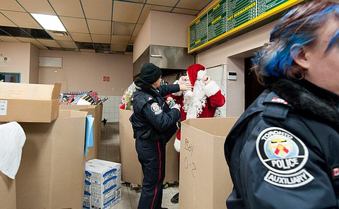 An Auxiliary officer helps Santa put on his hat.
