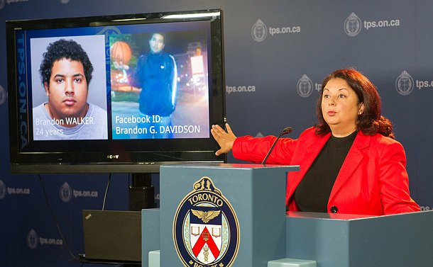 A woman at a podium pointing to  a TV with two photos of a man