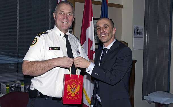 Two man in an office environment holding a gift bag that has a Montenegro crest on it