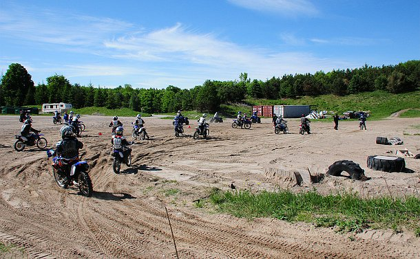 A group of people riding dirt bikes in an open dirt area