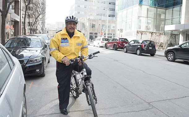 A man in TPS uniform on a street with a bicycle