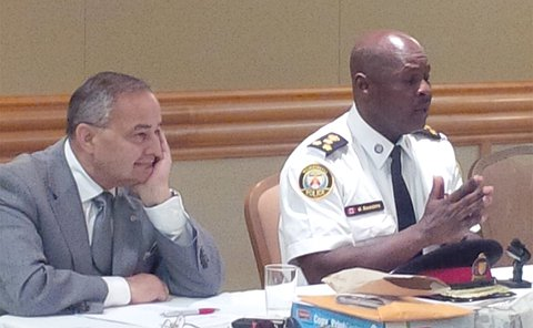 A man sits beside another man in TPS uniform at a table with microphones