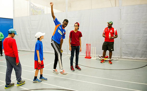 A man in a sports jersey showing a boy how to swing his arm when bowling