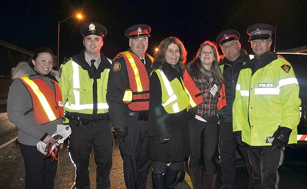 A row of men and women in police uniform and regular clothing but all wearing reflective vests, at night