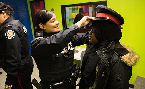 A woman in TPS uniform holds a hat on the head of a teenage girl