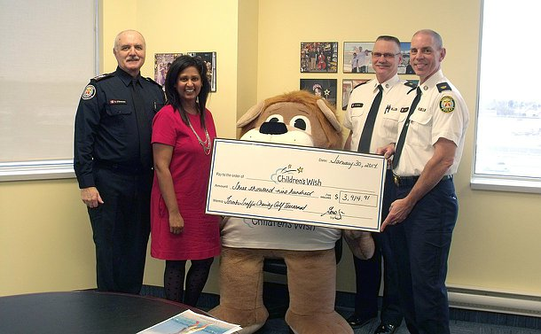A group of three men in Toronto Police uniform with a woman and a large stuffed animal with a oversized cheque