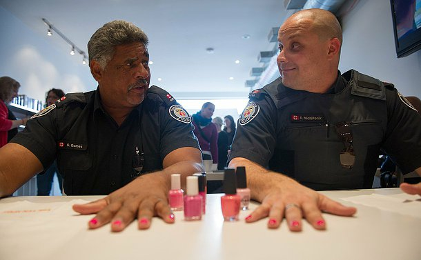 Two officers sit next to each other getting their nails done and talking.