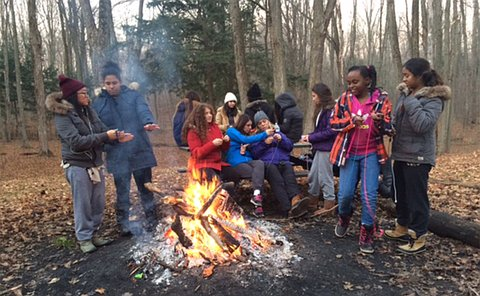 A group of people near a campfire in a wooded area