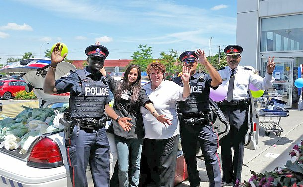 Three men in TPS uniform with two women in front of a TPS car