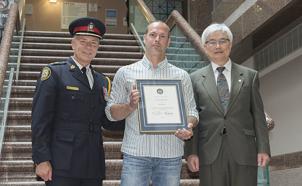 A man in TPS uniform with two men, one holds a framed certificate