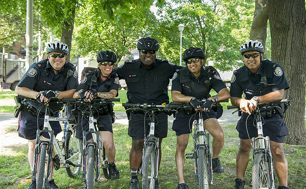 A group of five officers in TPS uniform on bikes in a treed setting