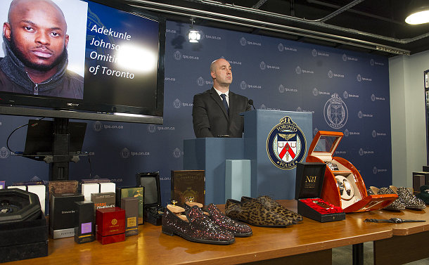 A man at a podium behind a table with watches, colognes, shoes and TV with a close up of a man