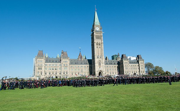 A wide shot, parliament building in the background, in the foreground officers are marching in to line up