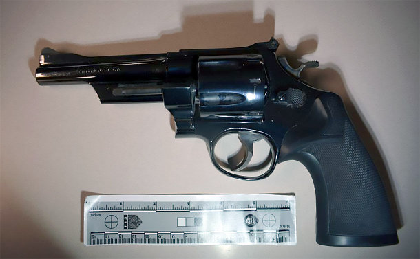 Photo of a firearm with a size ruler below it.