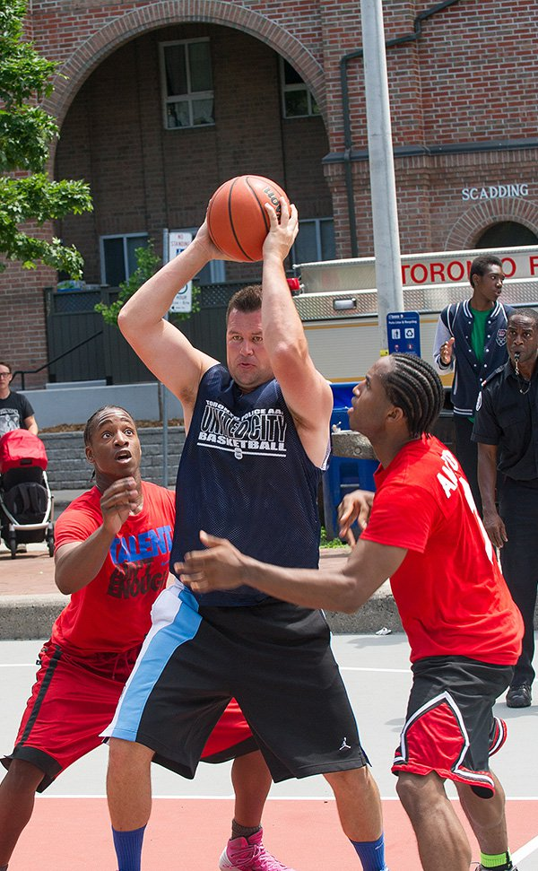 A tall man with his arms over his head and a basketball in his hands is surrounded by two young men in red basketball jerseys trying to block him.