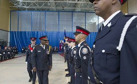 A group of men in TPS uniform walk past a line of TPS officers