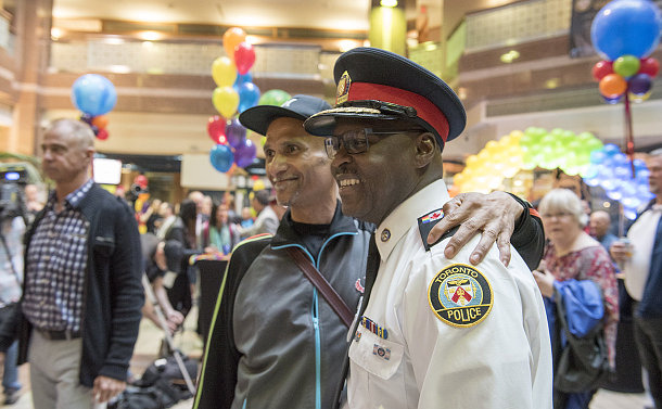 A man in TPS uniform with another man
