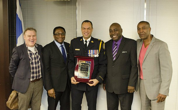 Five men, one in centre in TPS uniform holding a framed certificate