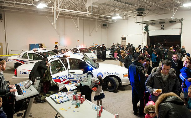 A garage filled with police vehicles and people