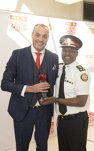A man accepts an award from a man in TPS uniform