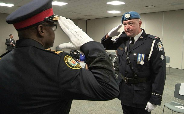 Two men in TPS uniform salute each other