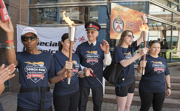 Five people, two holding torches