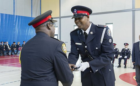 A man in TPS uniform shakes hands with another man in TPS uniform