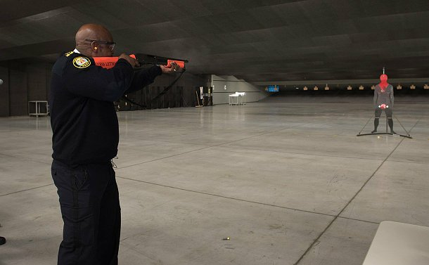 A man in TPS uniform points a shotgun with orange markings at a person-like target