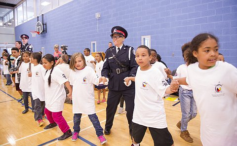 A woman in TPS uniform holding hands with children dressed in white T-shirts