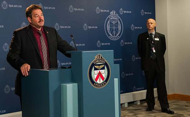 A man speaks at a podium while another man standing nearby looks on