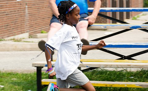 A girl with a blue and red hairband runs on an outdoor track.